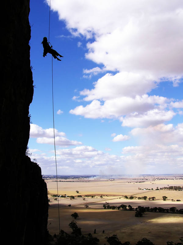 person belaying off cliff