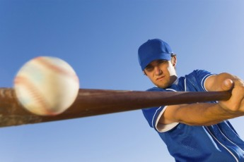 baseball player hitting ball with bat