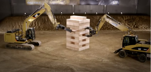 giant earth-movers playing jenga