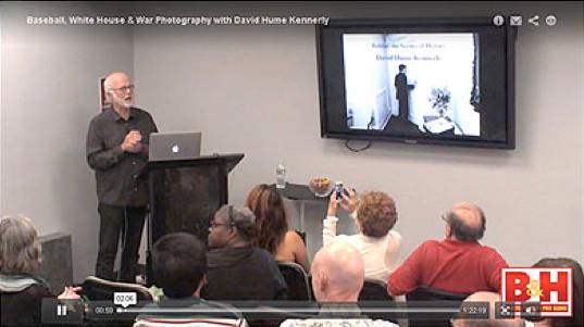 man behind podium speaking to group