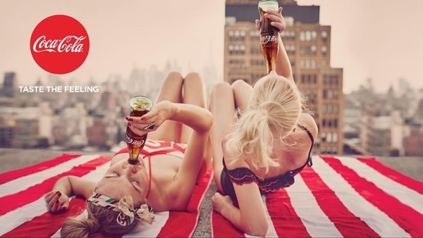 An image showing an example of an ad from Coca-Cola's Taste the Feeling campaign that uses the color red to great effect, drawing attention to the women drinking Cokes.