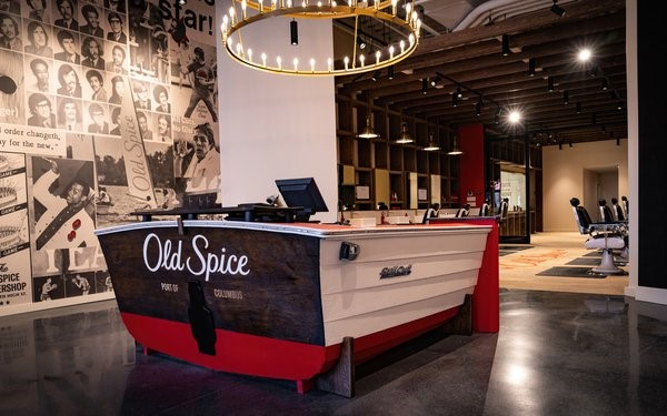 : An image showing the new Old Spice barbershop. The front desk is shaped like a boat, Old Spice ad images on the wall, and barbershop chairs fill the retail space.