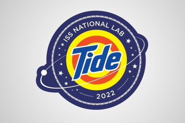 Image showing the ISS National Lab Nasa Tide logo. The first-ever astronaut laundry solution.